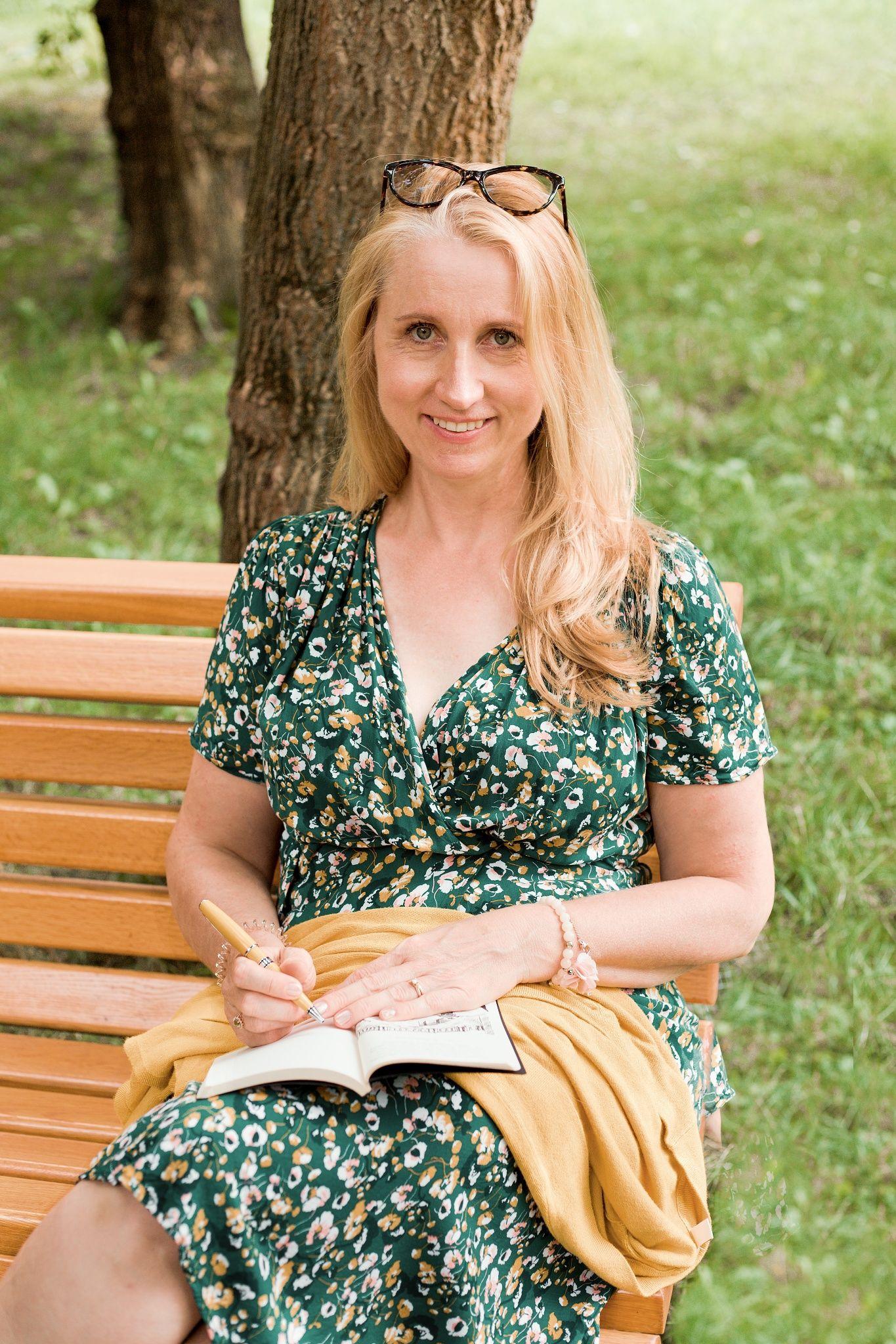 Diana Laurichová sedí na lavičce a čte